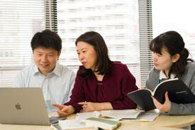 Hirano-Iwata in discussion with her laboratory staff. She finds the research environment at AIMR conducive to cooperative research.