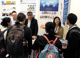 Staff at the World Premier International Research Center Initiative (WPI) exhibition booth at the 2019 E-MRS Spring Meeting interacting with visitors.